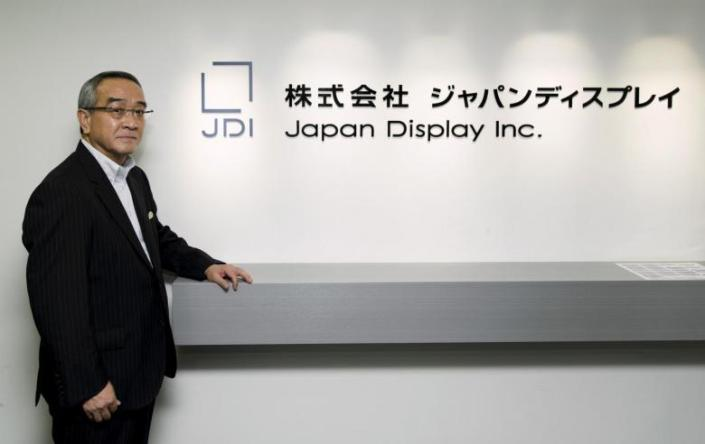 Japan Display Inc Chief Executive Mitsuru Homma poses in front of the company's logo at its headquarters in Tokyo September 3, 2015.  REUTERS/Thomas Peter