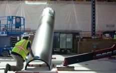 """Un operario vigila cómo levantan la recubierta de unas de las columnas que soportan el techo de la """"spaceship""""."""