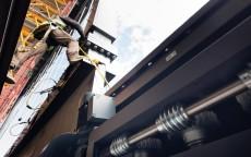Un operario trabaja en el sistema de raíles que abrirá las grandes puertas acristaladas del edificio principal del Campus 2.